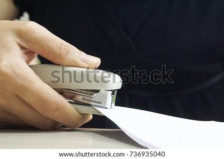 Woman hand holding a stapler, close-up.