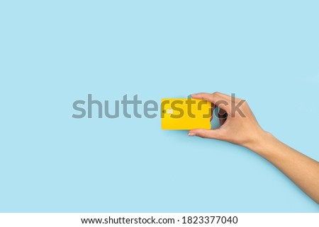 Woman hand holding a yellow credit card on a light blue background Foto stock ©