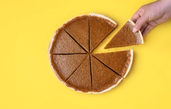 Woman hand holding and taking a piece of pumpkin pie on a yellow background. Above view of traditional autumn dessert. Thanksgiving sweet food. Eating pie.