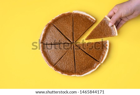 Woman hand holding and taking a piece of pumpkin pie on a yellow background. Above view of traditional autumn dessert. Thanksgiving sweet food. Eating pie. #1465844171
