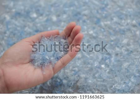 Woman hand holding Bottle flake,PET bottle flake,Plastic bottle crushed,Small pieces of cut blue plastic bottles