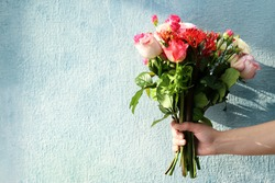 Woman hand holding bouquet of fresh flowers on light background
