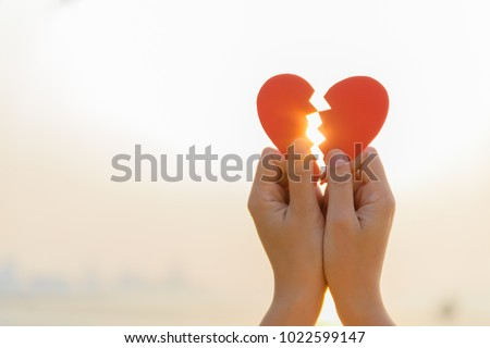 Woman hand holding broken paper red heart on sunset. Love, Wedding and Valentines day concept.