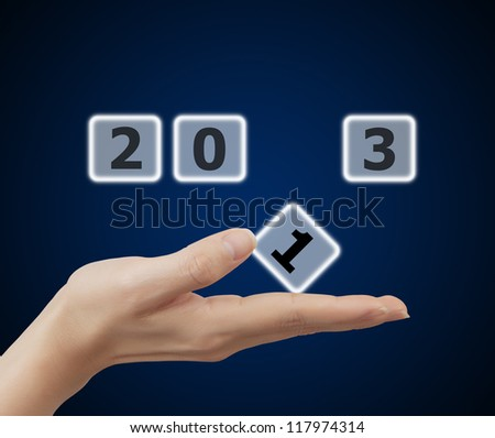 woman hand holding button 2013 keyword, on blue background