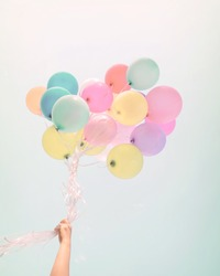 Woman hand holding colorful balloons. happy birthday party in summer holidays - pastel color filter