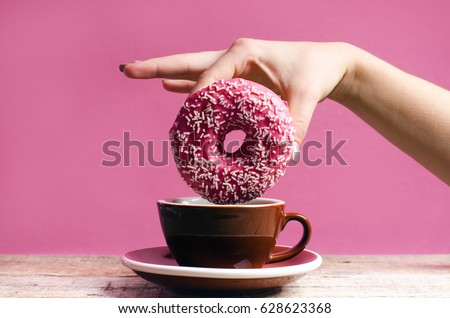 Woman hand holding colorful donut with sprinkles on a wooden table and pink background. Cup of coffee. Concept of food. Donut with bite missing Pastel color