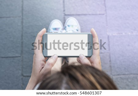 Woman hand holding contemporary modern smartphone. Visual effects. Blank display replaceable with needed design.Horizontal mockup