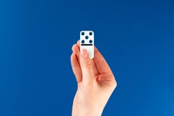 Woman hand holding domino piece  against blue background, top view