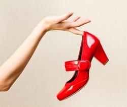 Woman hand holding dress red high heels shoe.