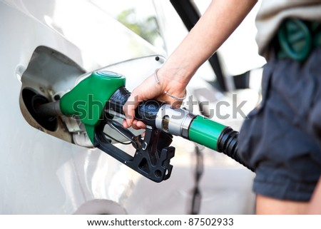 woman hand holding fuel nozzle and refuel car in gas station - stock photo