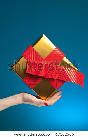 woman hand holding gift box on blue background