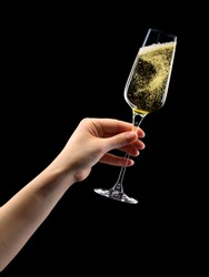 Woman hand holding glass of sparkling champagne isolated on black background.