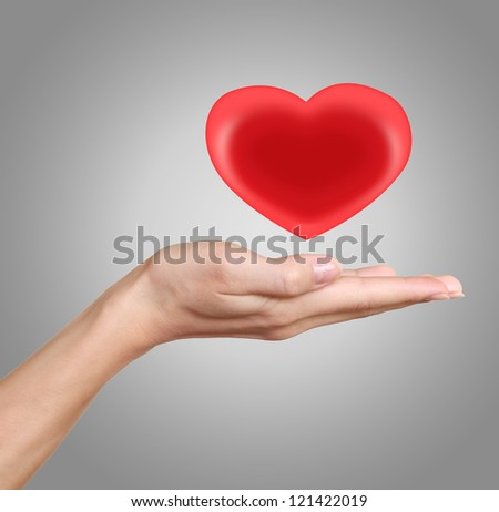 Woman hand holding heart, red and bright. Love and heath symbol isolated on grey background