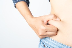 Woman hand holding her own belly fat and cellulite on white background. Women before weight loss and shape up healthy stomach muscle concept.