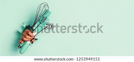 Woman hand holding kitchen utensils on blue background. Baking tools - brush, whisk, spatula. Bakery, cooking, healthy homemade food concept. Copy space. #1253949151