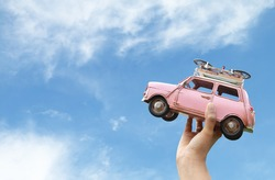 woman hand holding miniature car with blue sky and clouds,(travel concept)