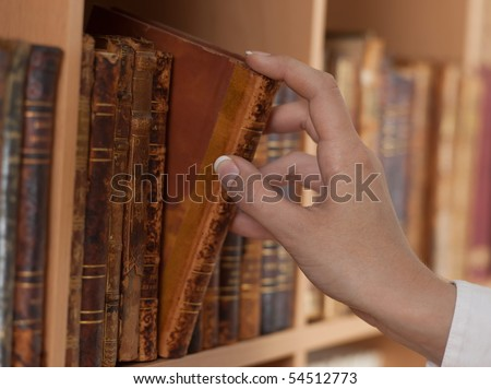 woman hand holding old book library close up - stock photo