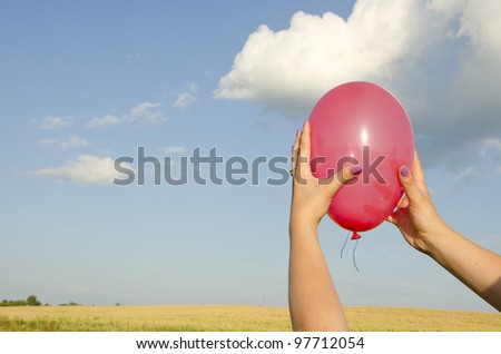 Woman hand holding red balloon on background of sky and farm fields.