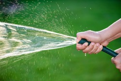 Woman hand holding rubber water hose and using finger close end of rubber water hose to make  water spray with sunlight and green grass field in background. World Water Day conpect.