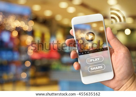 Woman hand holding smartphone against blur bokeh of shop background VDO ads concept