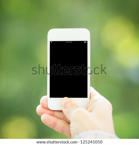 Woman hand holding smartphone against spring green background
