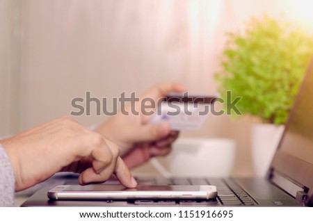Woman hand holding smartphone and using credit card at home for online shopping is a form of electronic commerce is a transaction of buying or selling goods or services online over the internet.