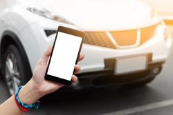 Woman hand holding smartphone isolated white screen on road with white car background