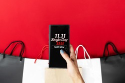 woman hand holding smartphone with shopping bag, China 11.11 single day sale concept
