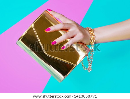 Woman hand holding the beautiful gold handbag