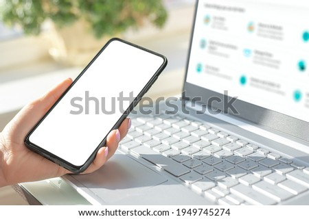 woman hand holding the black cell phone smartphone with blank white screen and modern frame less design on black background. Mockup phone. hand holding mobile phone. Mockup cell phone on laptop