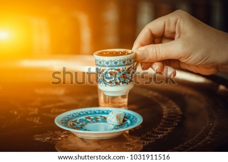 woman hand holding traditional porcelain turkish coffee cup