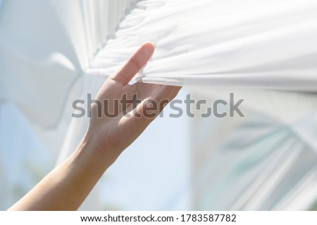 Woman hand holding white clean fabric curtain drape or clothes outdoor gently after use sunlight dry fabric after laundry. Concept of housewife washing clothes in weekend lifestyle.