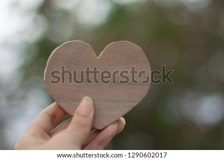 Woman Hand holding wood heart on blurred green background,love valentine's day concept. #1290602017