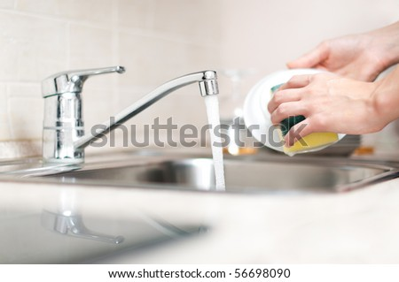 woman hand holding yellow sponge and washing saucer with washed dishes in background