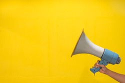 Woman hand holds magaphone,yellow background,copy space,selective focus