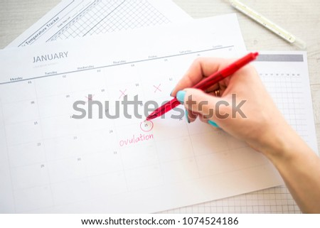woman hand holds red highlighter with temperature mark on calendar, Concept of fertility chart, trying to have baby and natural contraception, Reminder Ovulation in graph, Planning of pregnancy Stock photo ©