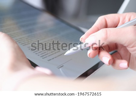 Woman hand holds stylus and puts an electronic signature in contract on tablet Foto stock ©