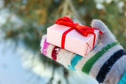 Woman hand in knitted mitten holding gift on winter background