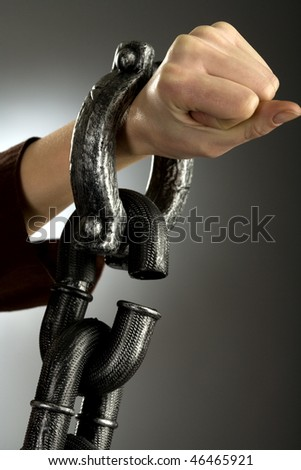 Woman hand in large handcuffs, gray background