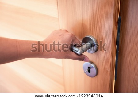 Woman Hand is Holding Door Knob While Opening a Door in Bedroom, Lock Security System and Access Safety of Doorway., Interior Design of Doorknob Entering to Accessibility Private Room #1523946014