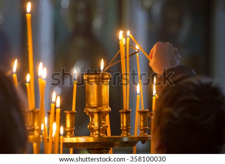 Woman hand lighting candles in a church.