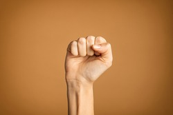 Woman hand making fist sign fighting for her rights. Hand with fingers folded into fist isolated on brown background. Fighting for women rights, against the violence and for equality and independence.