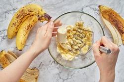 Woman hand mashing up several bananas to bake into a banana bread.