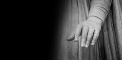 Woman hand on antique tunic. Stone statue detail of human hand. Folds in the fabric. Copyspace for text