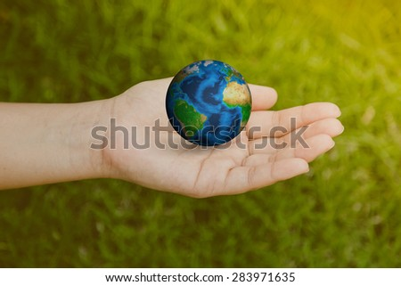 Woman hand on green grass ( Filtered image processed vintage effect. ) Woman hand on green grass ( Filtered image processed vintage effect. ) Elements of this image furnished by NASA