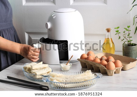 Woman Hand Open Airfryer Tray. A White Deep Fryer or Oil Free Fryer Appliance, Tongs, Clear Baking Dish and Egg Tray are on the Wooden Table in the Kitchen with a Small Plant in the Pot (air fryer)