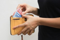 woman hand open wallet and showing rupiah money