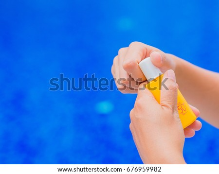Woman hand opened sunscreen / sunblock lotion by the swimming pool. Vacation and relaxation, summer travel concept. #676959982