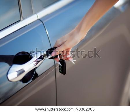 woman hand opening car door with key