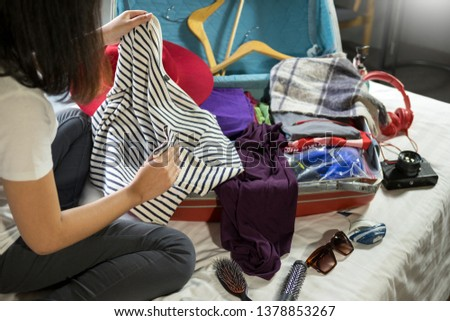 Woman hand packing a luggage for a new journey and travel for a long weekend #1378853267